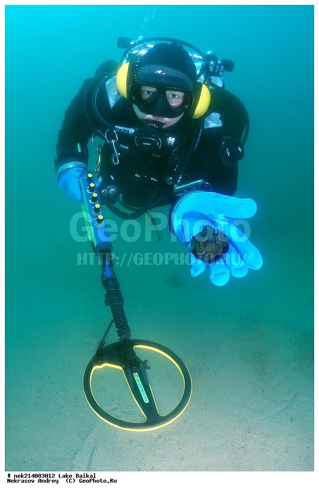 Фотография подводный археолог с металлоискателем под водой в.