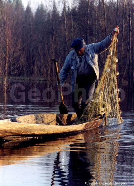 рыбак на лодке с сетью